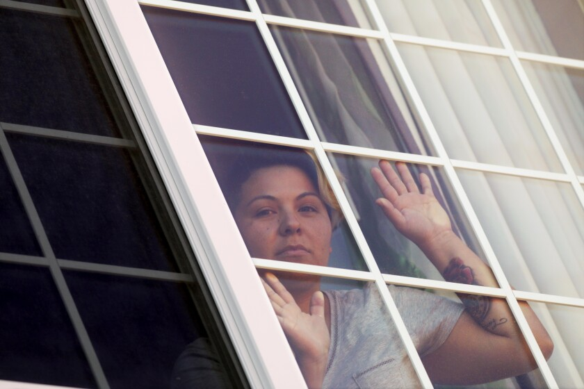 Maricela Ortiz, 31, who has COVID-19, looks out from her hotel room where she has been self-quarantined in Visalia on April 30. Ortiz tested positive after she was released from Otay Mesa Detention Facility in San Diego. She was denied a test despite having symptoms including fever, body chills and aches.