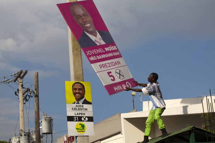 """FILE - In this Nov. 12, 2015 file photo, supporters of presidential candidate Maryse Narcisse, of the Lavalas party, removes an election campaign sign of presidential candidate Jovenel Moise, in front of a sign of his rival, Jude Celestin, during a protest against election results in Port-au-Prince, Haiti. Celestin and the other presidential candidates that dub themselves the """"Group of Eight"""" have been demanding an independent recount due to what they assert was """"massive fraud"""" in favor of Moise, the government-backed contender in October elections. (AP Photo/Dieu Nalio Chery, File)"""
