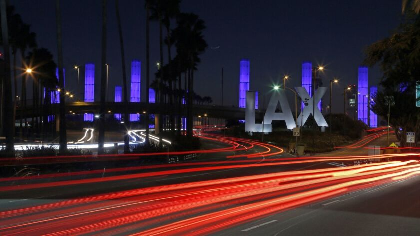 Lighted pylons and cars create a light show on Century Boulevard, near the entrance to Los Angeles International Airport. The airport plans to install new technology in a bathroom at Terminal 4 to help keep them cleaner and notify passengers when a stall is vacant.