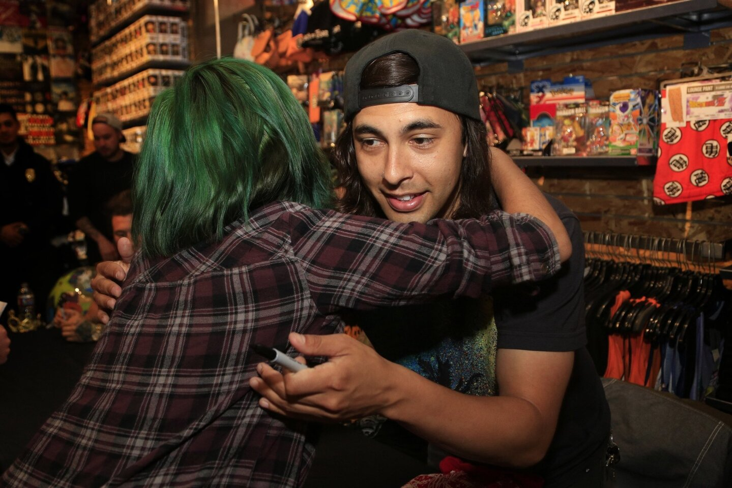 Vic Fuentes of Pierce the Veil hugs a fan during an album signing event at Hot Topic at Westfield Mission Valley mall.