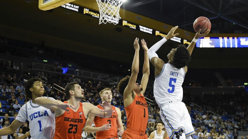 UCLA guard Chris Smith, right, drives for a layup while Oregon State guard Stephen Thompson Jr., second from right, defends during the second half.