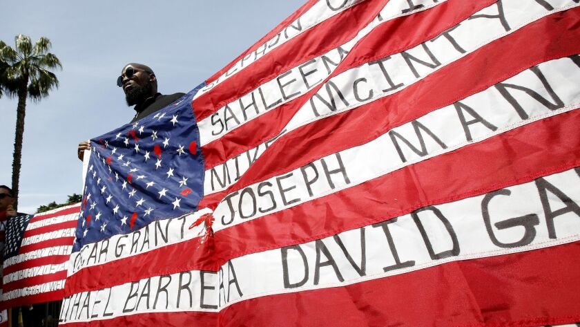 Malaki Seku Amen holds up an American flag with the names of people shot and killed by law enforcement officers, as he joins others April 8 in Sacramento in support of a bill that would restrict the use of deadly force by police.