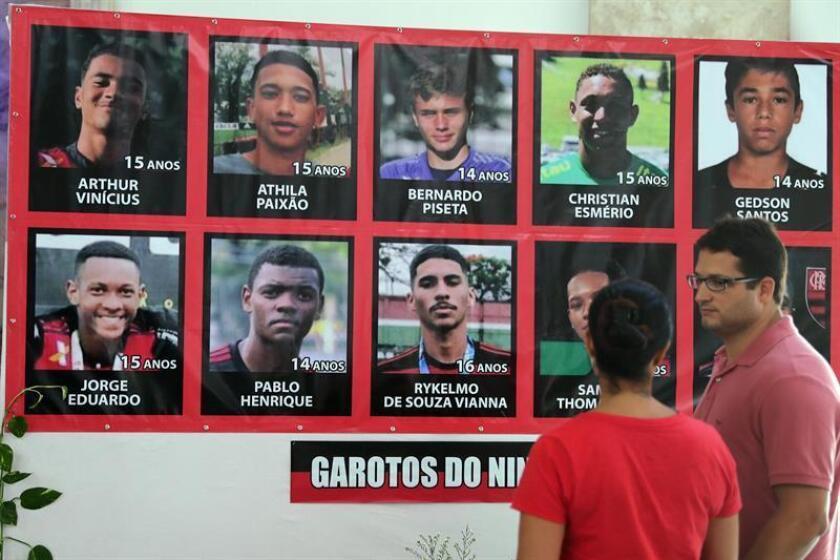 Fotografía tomada el pasado 15 de febrero en la que se registró a dos personas al observar una pancarta con las fotos de los diez adolescentes muertos en el incendio de un centro de entrenamiento del club brasileño de fútbol Flamengo, en Río de Janeiro (Brasil). EFE/Archivo