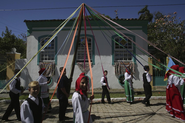 En esta imagen un grupo folclórico interpreta una danza con lazos en torno al poste de San Sebastián, durante el Festival de Cultura Azoriana, que celebra las tradiciones de las Azores, en Enseada de Brito, en el estado brasileño de Santa Catarina. (AP Foto/Eraldo Peres)