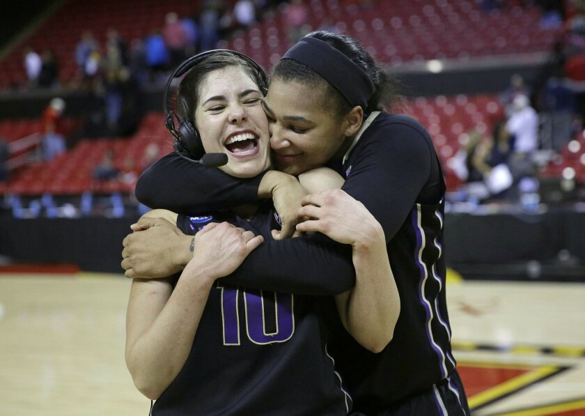 Washington forward Talia Walton, right, hugs teammate Kelsey Plum as Plum speaks on a television interview after an NCAA college basketball game against Maryland in the second round of the NCAA tournament, Monday, March 21, 2016, in College Park, Md. Plum contributed a game-high 32 points to Washington's 74-65 win. (AP Photo/Patrick Semansky)