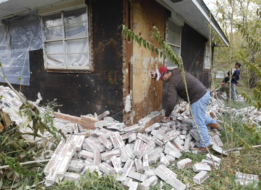 Chad Devereaux examines bricks that fell from three sides of his in-law's home in Sparks, Okla., on Nov. 6, 2011, after two earthquakes hit the area in less than 24 hours. A team of scientists has determined that a 5.6 magnitude quake in Oklahoma in 2011 was caused when oil drilling waste was injected deep underground.
