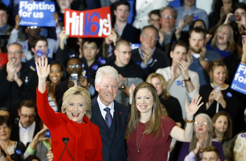 La precandidata demócrata Hillary Clinton, acompañada por su esposo el ex presidente Bill Clinton y su hija Chelsea, saluda en un evento electoral el 1 de febrero de 2016 en Des Moines, Iowa. Clinton y su rival Bernie Sanders estaban empatados en las asambleas partidarias de Iowa. (AP Foto/Patrick Semansky)