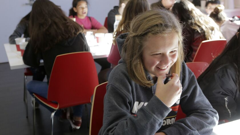 Vista Christian School seventh-grader Claire McLeod, 12, enjoys a sample of a Mintfully Brownie Bar at its unveiling Wednesday at Chuao Chocolatier in Carlsbad. She was head chef in the classroom candy-making project that inspired Chuao CEO Michael Antonorsi.