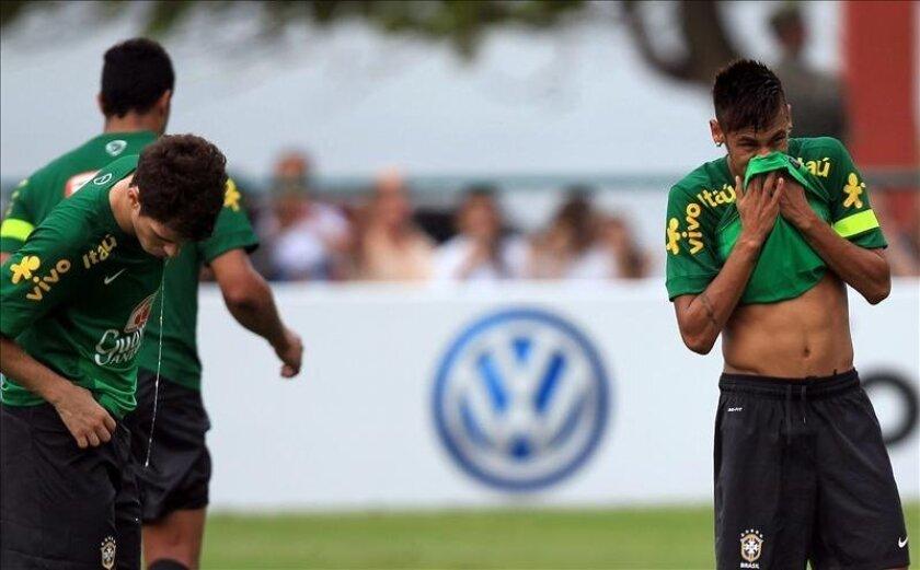 Los jugadores de la selección brasileña de fútbol, Óscar (i) y Neymar (d), participan, este miércoles 29 de mayo, en el primer entrenamiento del equipo para el partido del próximo domingo 2 de junio ante el seleccionado de Inglaterra, en el estadio de Maracaná de la ciudad de Río de Janeiro. EFE