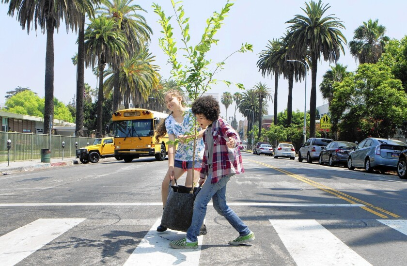 Maria Flor, 10, left, and Max Oppenheimer, 12, students in the youth outreach group Heart of Los Angeles, carry a plum tree to MacArthur Park, part of a public project to create a fruit tree trail that will wind its way through the neighborhood.