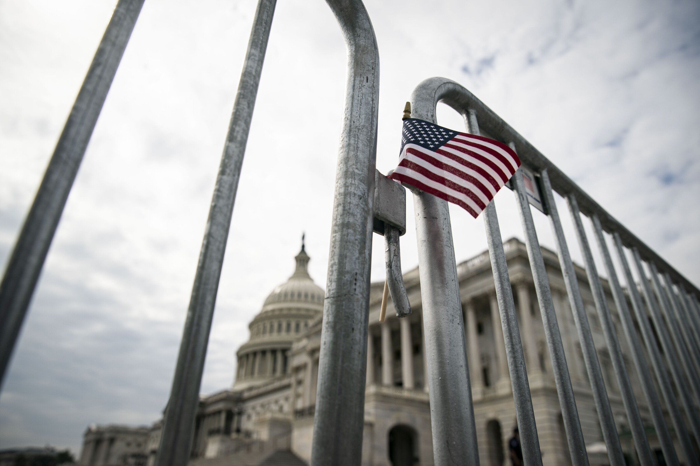 A small American flag on a fence outside the Capitol in Washington.