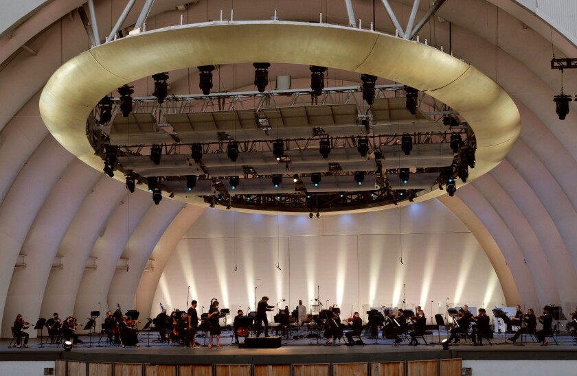 A conductor leads an orchestra on a stage.