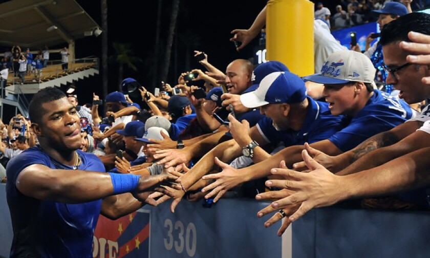 Dodgers right fielder Yasiel Puig celebrates with fans after the team's win over the Atlanta Braves in Game 4 of the National League division series at Dodger Stadium on Oct. 7, 2014.