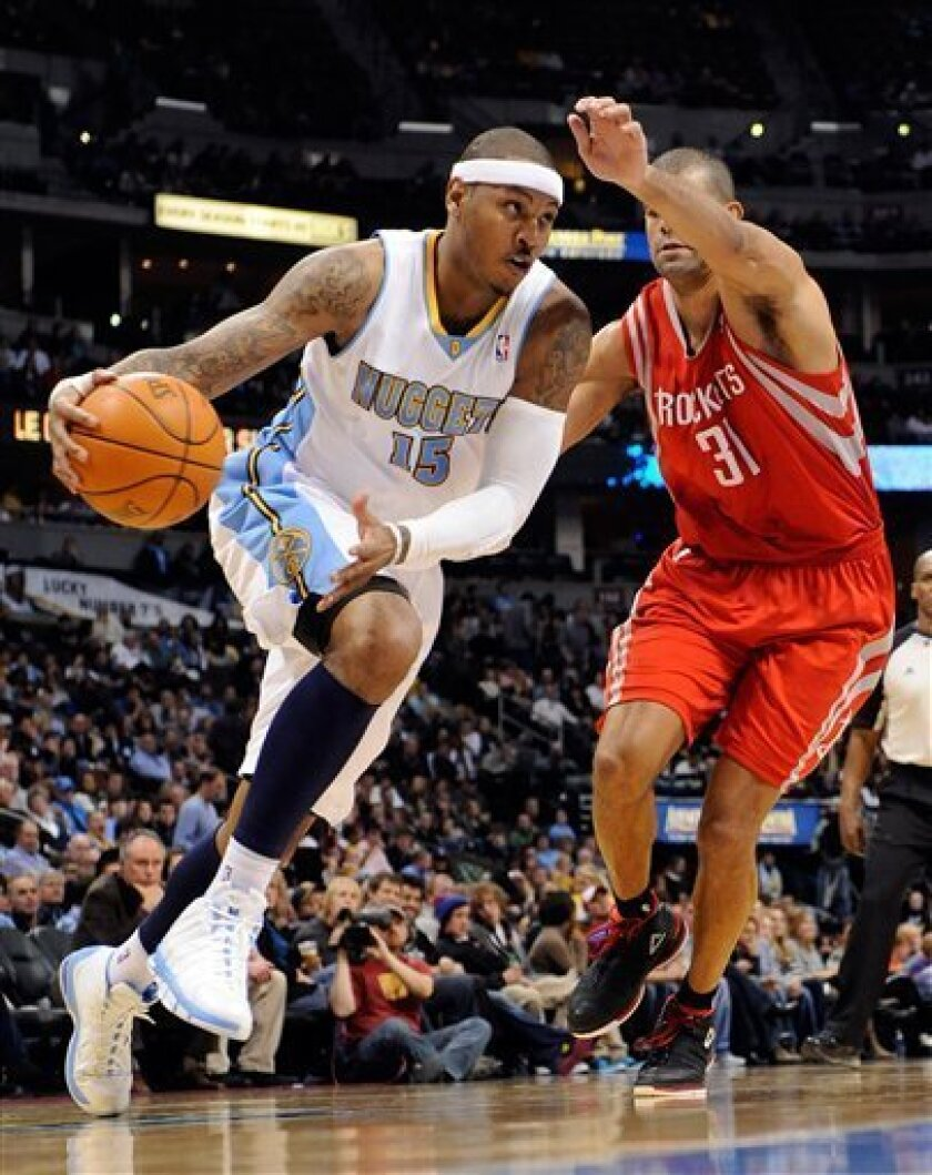 Denver Nuggets forward Carmelo Anthony (15) drives past Houston Rockets small forward Shane Battier (31) during the third quarter of an NBA basketball game Monday, Jan. 3, 2011, in Denver. (AP Photo/Jack Dempsey)
