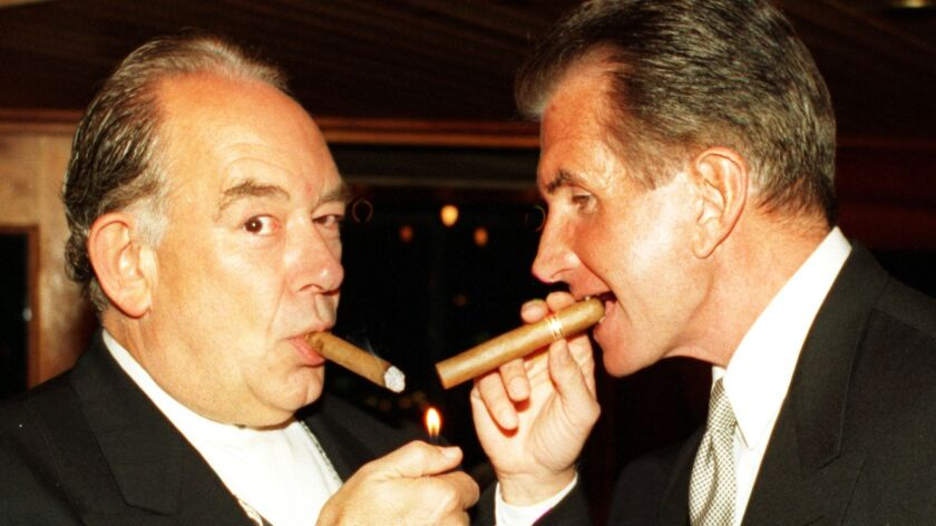 TV personality Robin Leach and actor George Hamilton puff on cigars during the James Beard Foundation of New York benefit.