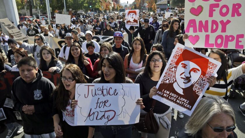 Protesters march on Tuesday, Oct. 29, 2013, in Santa Rosa, Calif. Hundreds of people have gathered