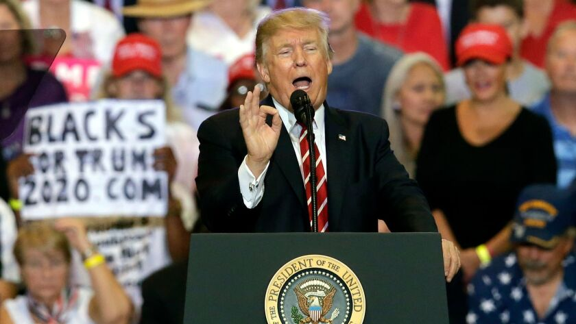 President Donald Trump gestures to the crowd while speaking at a rally at the Phoenix Convention Cen