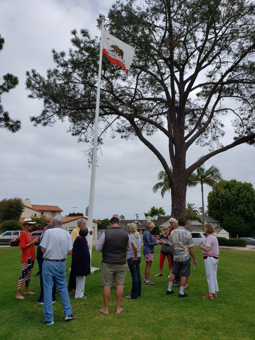 Supporters gather around the refurbished flagpole.