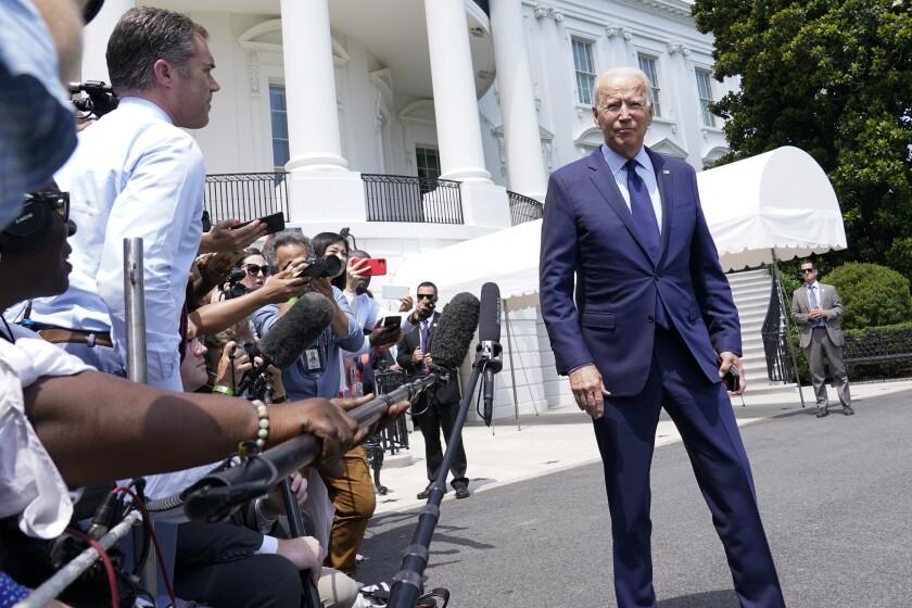 President Biden talks to reporters outside the White House