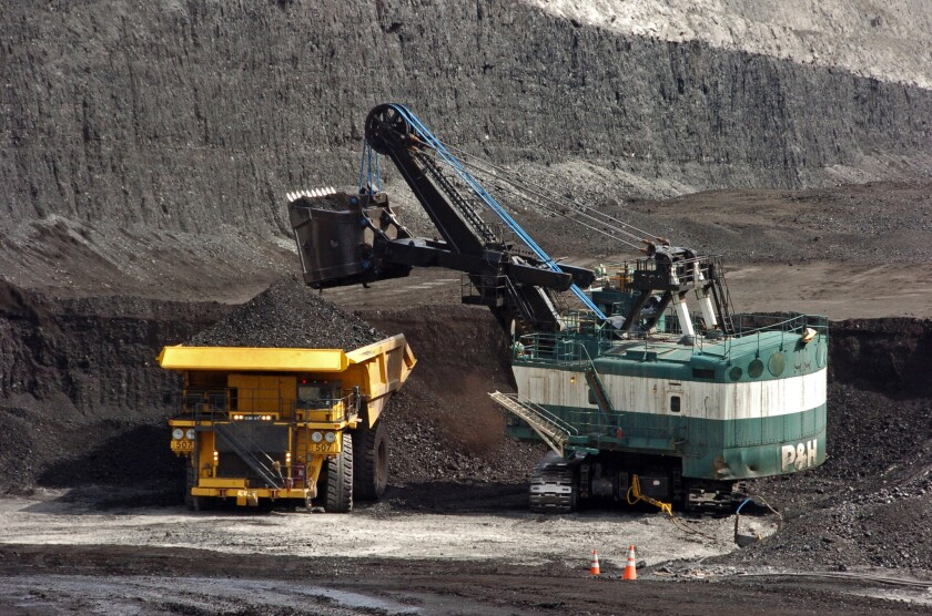 A machine loads coal onto a truck at a mine in Montana in 2013. A divided Supreme Court has agreed to halt enforcement of President Obama's plan to address climate change until after legal challenges are resolved.