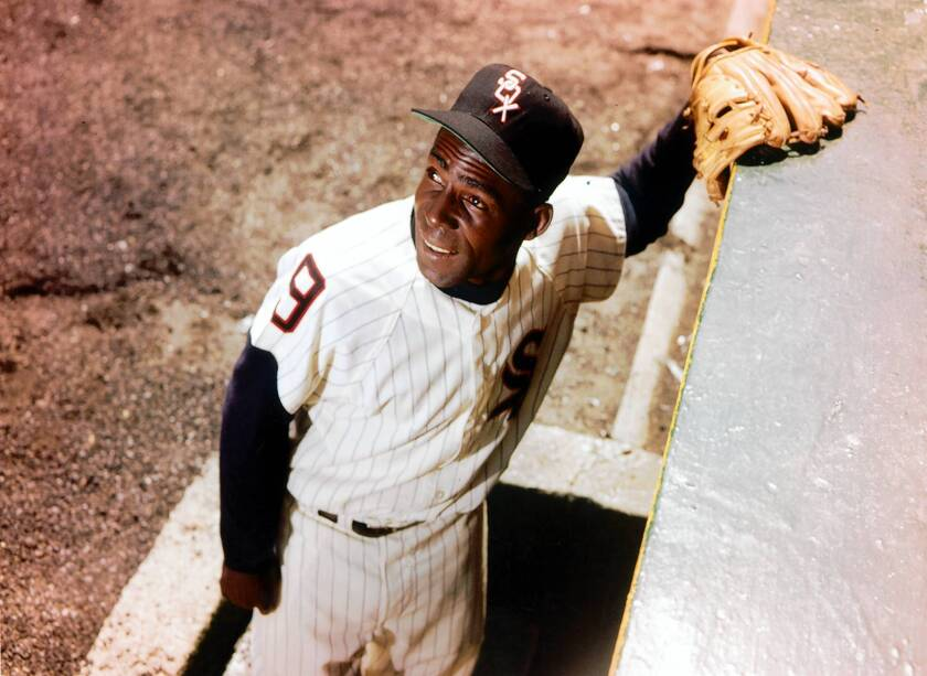 Chicago White Sox star Minnie Minoso poses outside the Comiskey Park dugout in 1960.