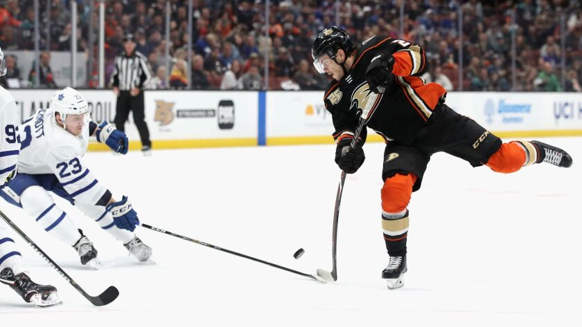 Ducks' Pontus Aberg shoots the puck as Toronto Maple Leafs' Travis Dermott defends during the third period on Friday at the Honda Center.