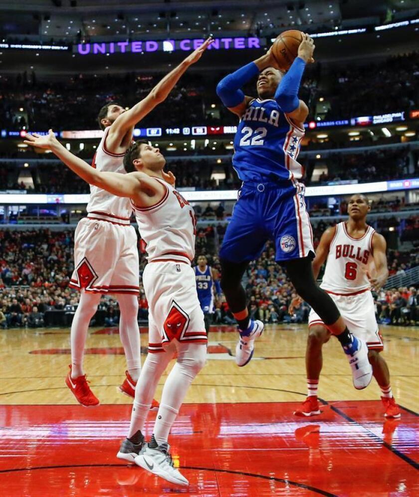 Richaun Holmes (d) de los 76ers ante Doug McDermott (c) y Nikola Mirotic (i) de los Bulls, durante el partido de la NBA disputado esta noche en el United Center de Chicago, Illinois. EFE