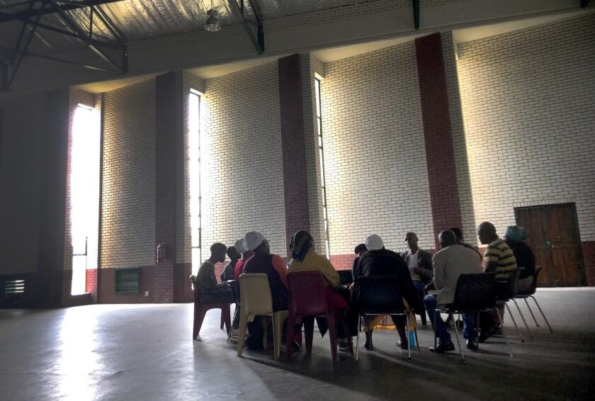 A group meets in a community hall in Brits, South Africa, to talk about drug addiction in their comm