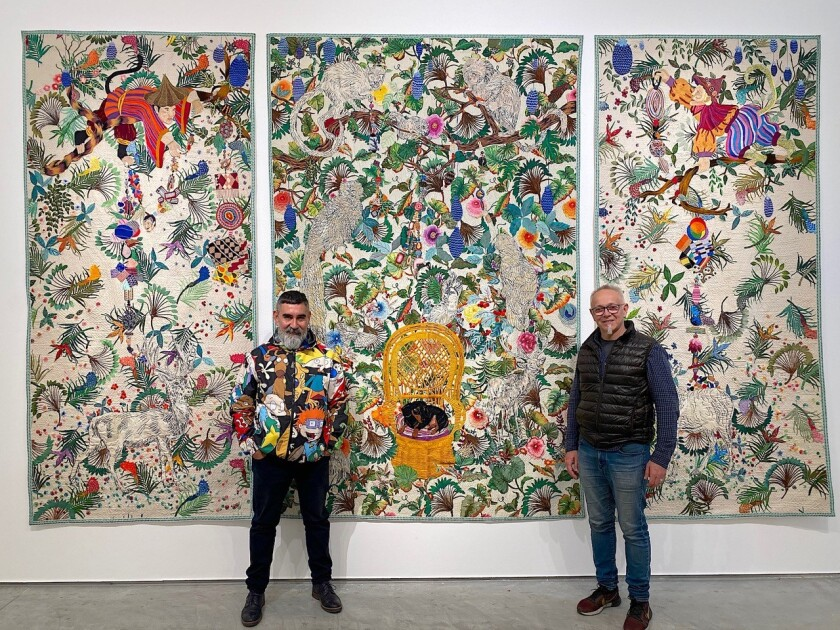 "Leo Chiachio and Daniel Giannone pose with ""Selva Blanca,"" (White Forest), a triptych that took them three years to complete. In the upper corners are portraits of the artists as costumed monkeys. In the golden chair is their No. 1 dog, Piolin, now 15 years old."