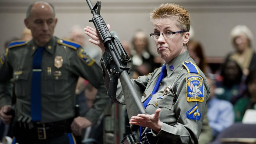 A firearms training unit detective holds a Bushmaster AR-15 rifle, the same make and model used by Adam Lanza in the 2012 Sandy Hook School shooting, during a hearing in Hartford, Conn. on Jan. 28, 2013.