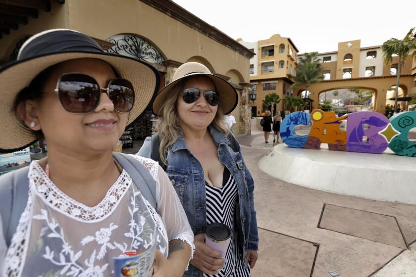 At the marina in Cabo San Lucas, Naomi Alcazar, 40, of Oxnard and Esperanza Barragan, 38, of Ventura are enjoying a vacation, but still worry about the coronavirus.