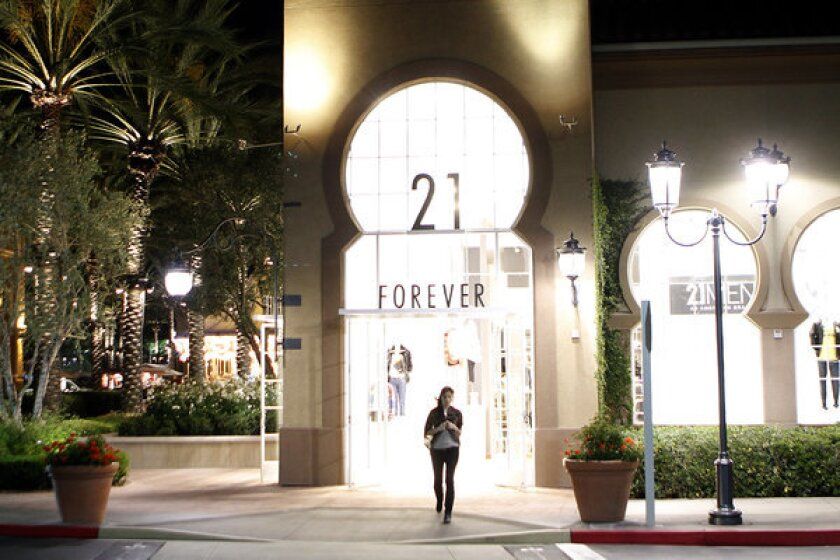 A woman walks out of a store at the Irvine Spectrum shopping center.