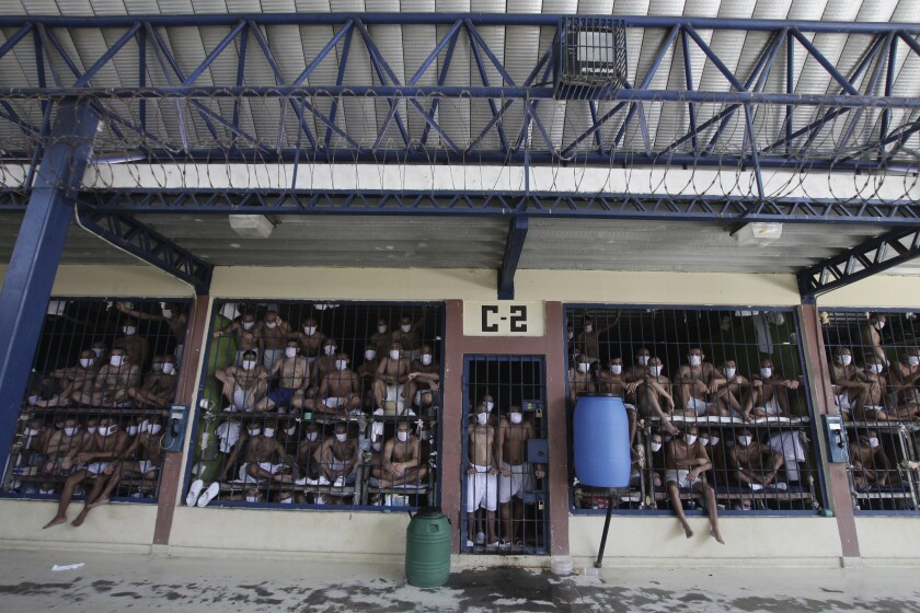 Imprisoned gang members, wearing protective face masks, look out from behind bars during a media tour of the prison in Quezaltepeque, El Salvador, Friday, Sept. 4, 2020. President Nayib Bukele denied a report Friday that his government has been negotiating with one of the country's most powerful gangs to lower the murder rate and win their support in mid-term elections in exchange for prison privileges. (AP Photo/Salvador Melendez)