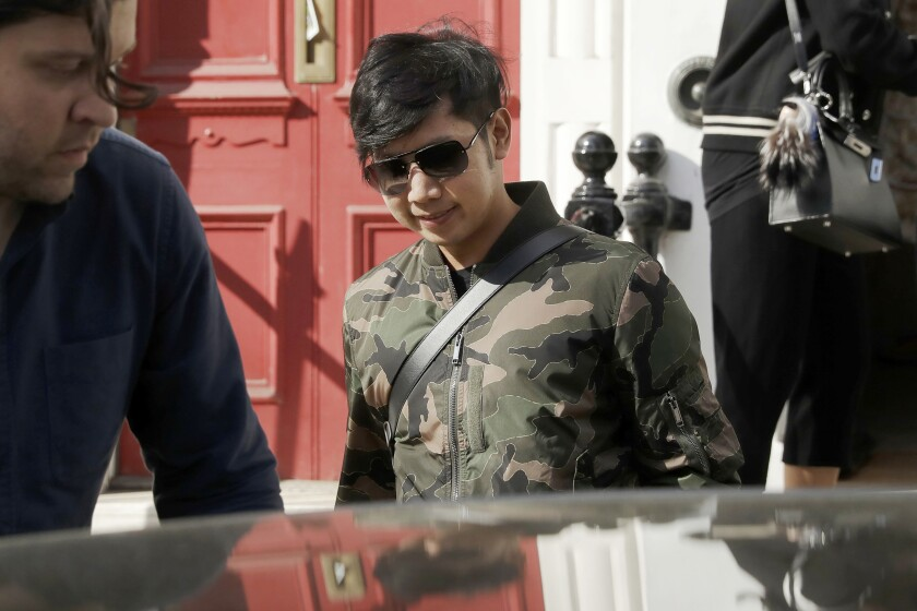 """FILE - In this April 5, 2017, file photo, Vorayuth """"Boss"""" Yoovidhya, whose grandfather co-founded energy drink company Red Bull, walks to get in a car as he leaves a house in London. A panel appointed by the Thai Prime Minister to look into the handling of the criminal case against an heir to the Red Bull energy drink fortune for a fatal hit-and-run incident has found there was a conspiracy to shield him from prosecution and recommended that those involved should face charges. (AP Photo/Matt Dunham, File)"""