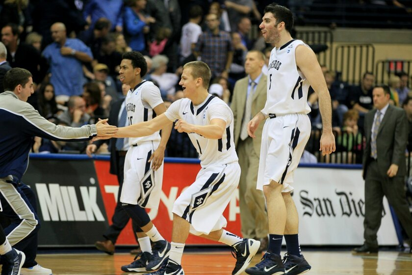 BYU at USD- USD's Johnny Dee, middle, shakes hands with redshirt teammate Nick Kerr, far left after USD's 74-68 victory over BYU.