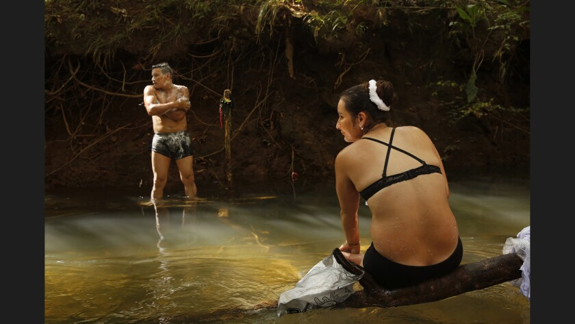 """Revolutionary Armed Forces of Colombia member Viviana, 28, and her comrade Jon, 34, bathe in spring waters by their camp. """"We're all kids of the same town and we've been killing each other,"""" Viviana says regarding the long war in the region between the FARC and paramilitary forces."""