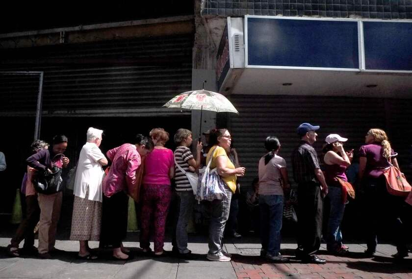 People line up to buy basic items outside a supermarket this week in Caracas. Once-booming Venezuela now suffers from shortages of food, medicine and basic goods.
