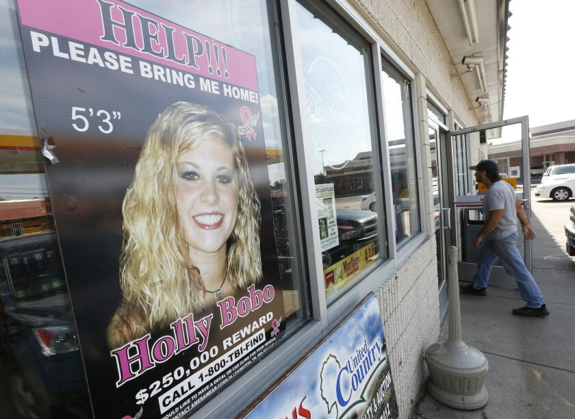 A poster offering a reward for information in the disappearance of Holly Bobo is displayed in a store window in Parsons, Tenn., on Tuesday, Sept. 9, 2014. The remains of Bobo, a nursing student who has been missing since April 2011, were found Sunday not far from her home in Parsons, according to officials. (AP Photo/Mark Humphrey)