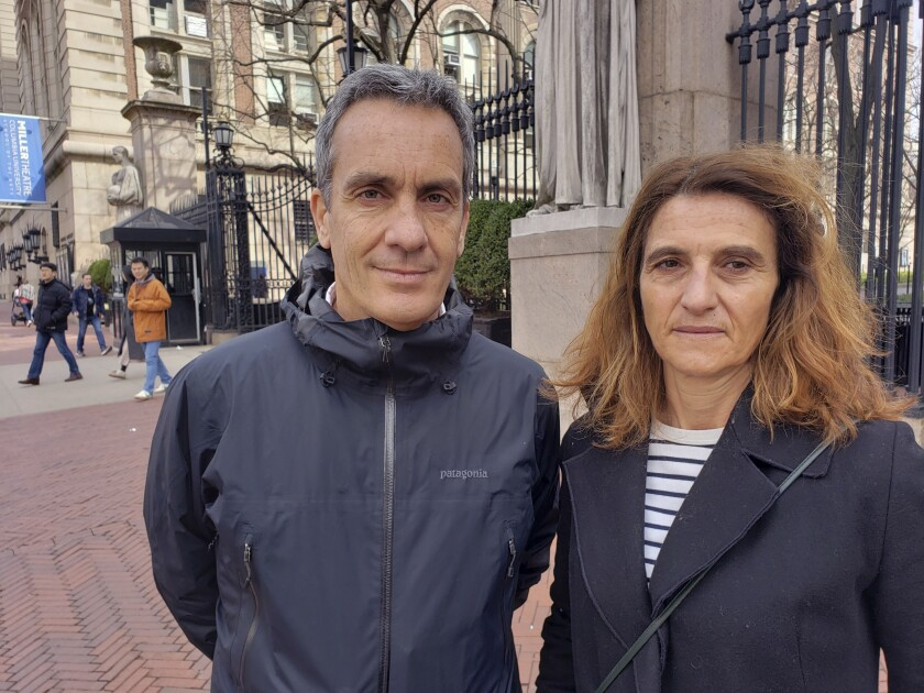 In this March 11, 2020 photo, Gianmarco de Felice and his wife, Annaelisa Lugini pose for a photo outside Columbia University in New York City. Italians in New York are worried for loved ones in Italy who are living under a nationwide lockdown to stem the spread of the new coronavirus. De Felice is in New York for a few months doing research. Lugini has been visiting and had been planning to return to Italy earlier this week, but decided to stay to avoid the lockdown. For most people, the new coronavirus causes only mild or moderate symptoms. For some it can cause more severe illness. (AP Photo/Juan Carlos Velasquez)
