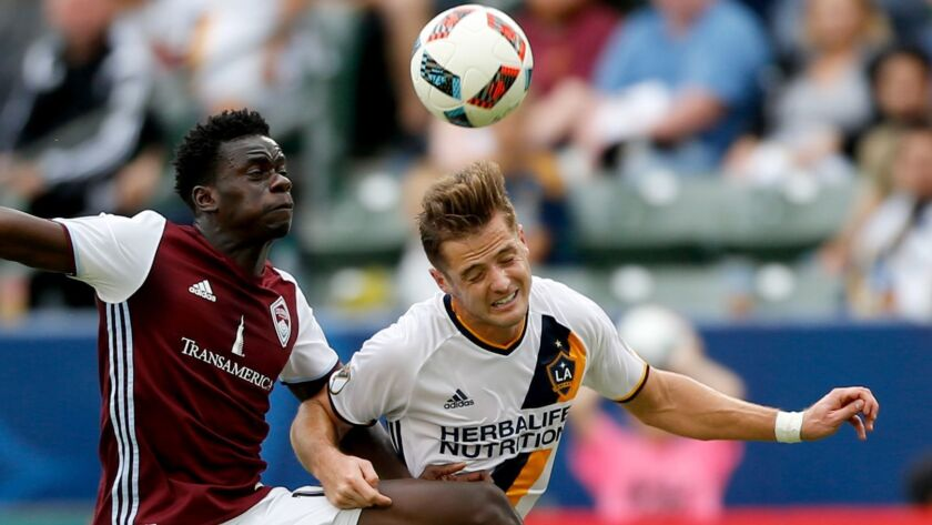 Galaxy forward Robbie Rogers, right, challenging Colorado Rapids forward Dominique Badji for the ball in MLS playoff game in 2016, is retiring.