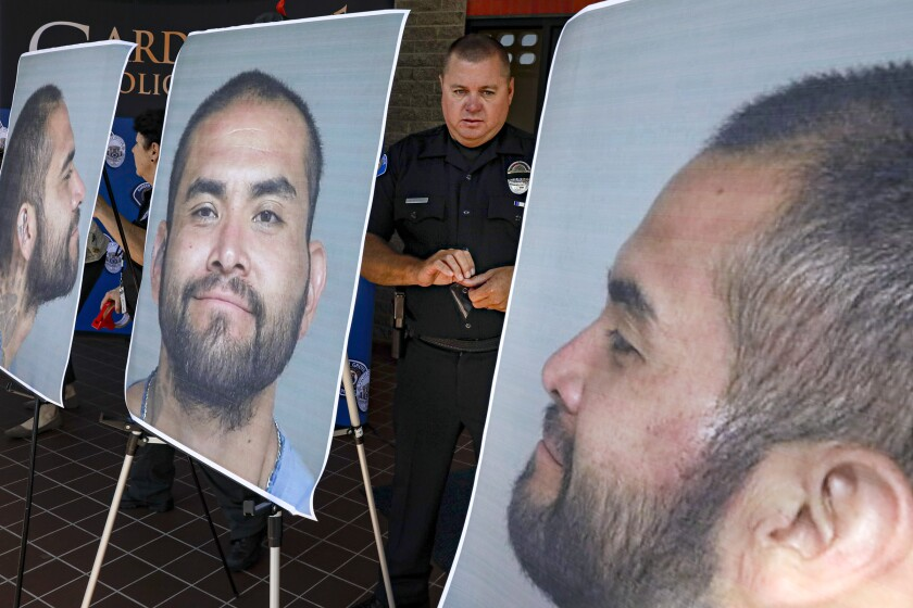 GARDEN GROVE, CA - AUGUST 08, 2019 — Cpl. Charles Starnes displays the photos of suspect Zachary Castaneda prior to a 1 pm press conference at Garden Grove police headquarters. (Irfan Khan/Los Angeles Times)