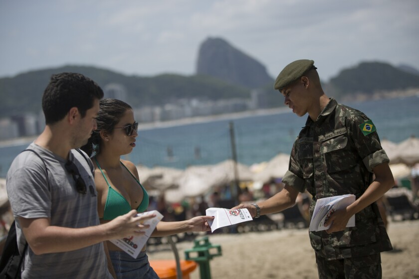 Brazilian soldier distributes pamphlets about the Aedes aegypti mosquito that spreads the Zika virus at the edge of Copacabana beach in Rio de Janeiro.
