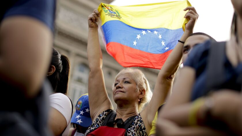 A Venezuelan anti-government protester holds a Venezuelan flag during a demonstration in Buenos Aire