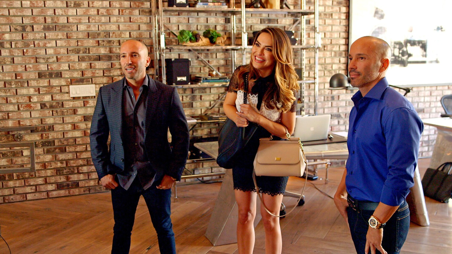 """Jason, left, and Brett Oppenheim introduce new recruit Chrishell Hartley to their firm's agents on Netflix's docu-soap """"Selling Sunset."""""""