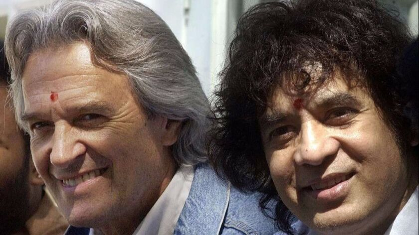 John McLaughlin (left) and Zakir Hussain are shown in India in 2003. In the mid-1970s, they co-found
