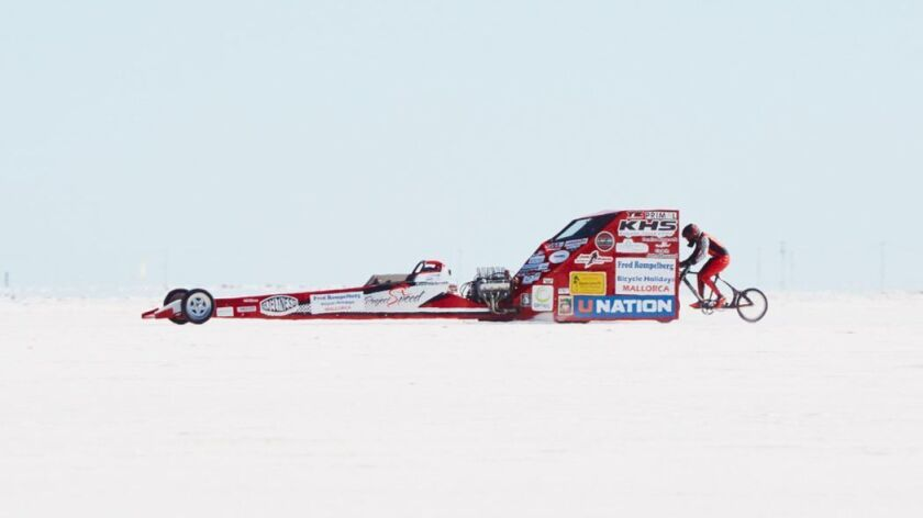 Denise Mueller-Korenek during her record-breaking ride to set the world's paced bicycle speed record on Sunday in Utah. She can be seen, at right, riding behind a modified dragster pace car.