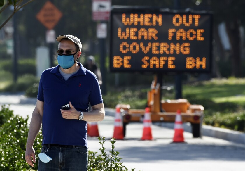 In a file photo, an electronic sign on Santa Monica Boulevard reminds people to wear masks .