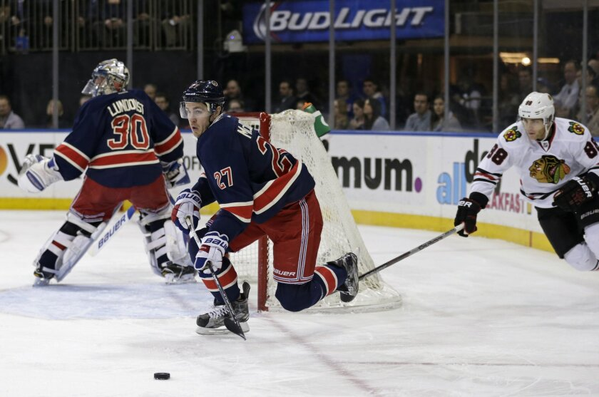 New York Rangers' Ryan McDonagh (27) looks to pass the puck in front of Chicago Blackhawks Patrick Kane (88) during the first period of an NHL hockey game Wednesday, Feb. 17, 2016, in New York. (AP Photo/Adam Hunger)