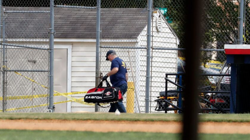 An FBI investigator removes a baseball bag from the Alexandria, VA. field where House Majority Whip Steve Scalise and others were during a congressional baseball practice.