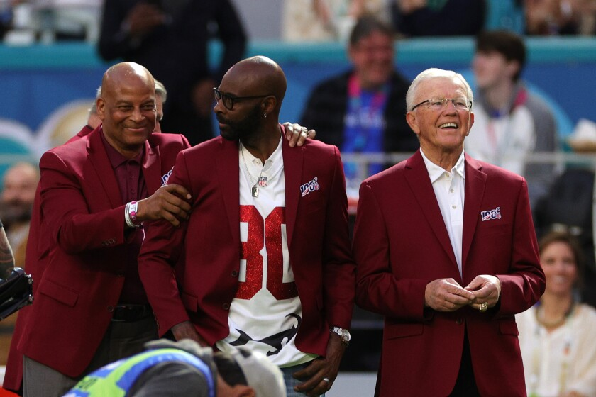 Former Washington Redskins coach Joe Gibbs, right, stands next to fellow Pro Football Hall of Famers Ronnie Lott, left, and Jerry Rice while being honored as part of the NFL's All-Time Team before Super Bowl LIV on Feb. 2.